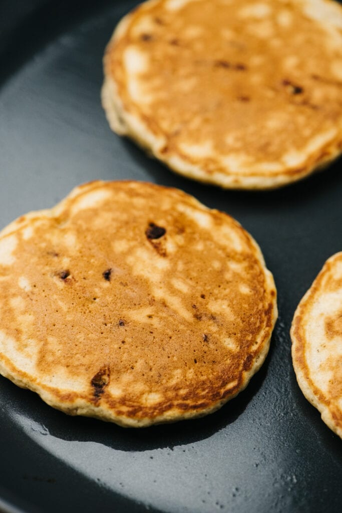 Side view, three pancakes on a skillet.