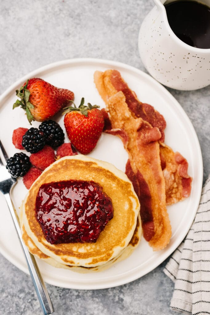 Pancakes topped with berry compote on a white plate with bacon and fresh berries.