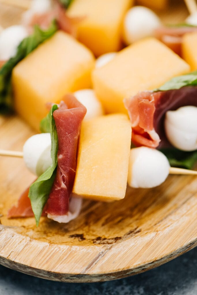 Side view, cantaloupe and prosciutto threaded onto toothpicks with basil and fresh mozzarella pearls.