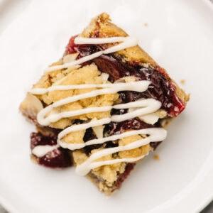 A single cherry pie bar with vanilla glaze on a white plate.