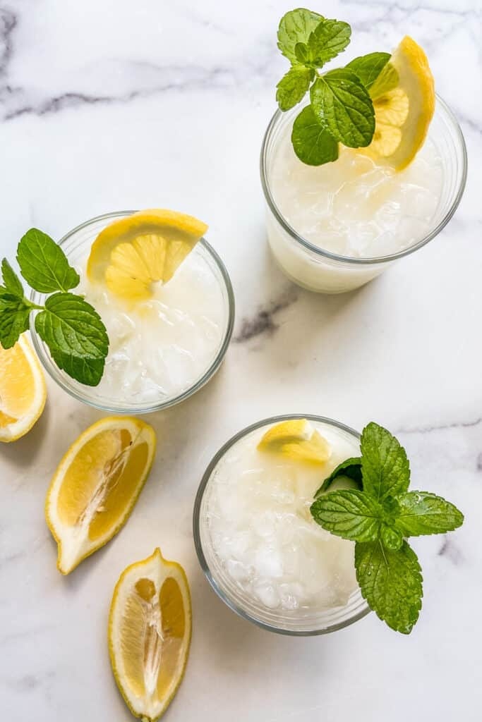 Three creamy lemonade drinks on a marble background with lemon wedges and mint leaves.