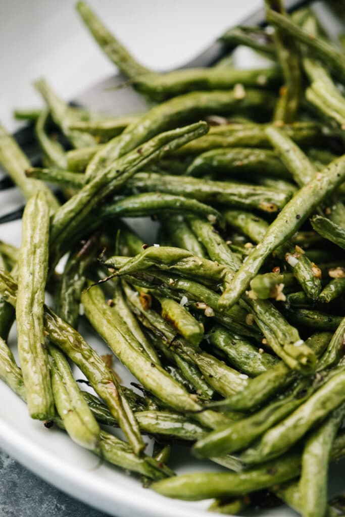 Side view, roasted green beans in a white serving bowl.