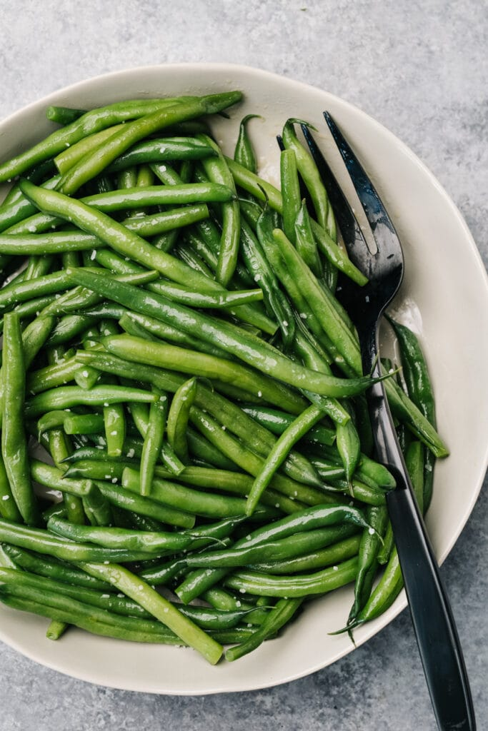 Steamed green beans in a tan serving bowl with a black serving fork.