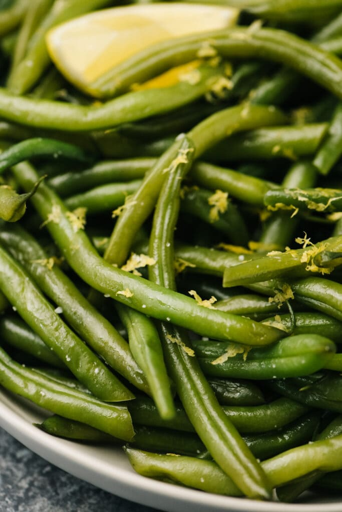 Side view, instant pot green beans in a white bowl garnished with lemon zest and a lemon wedge.