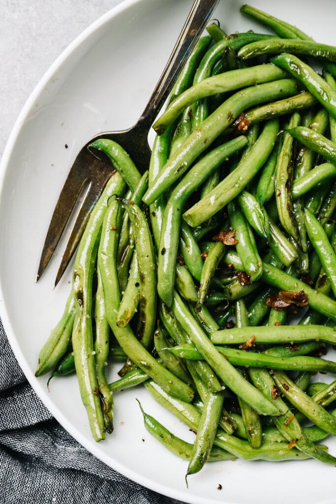 Sautéed green beans with garlic in a white serving bowl with a silver serving fork.