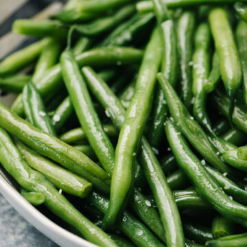 Side view, steamed green beans with butter, salt and pepper in a tan serving bowl.