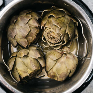 Four whole steamed artichokes in an instant pot.