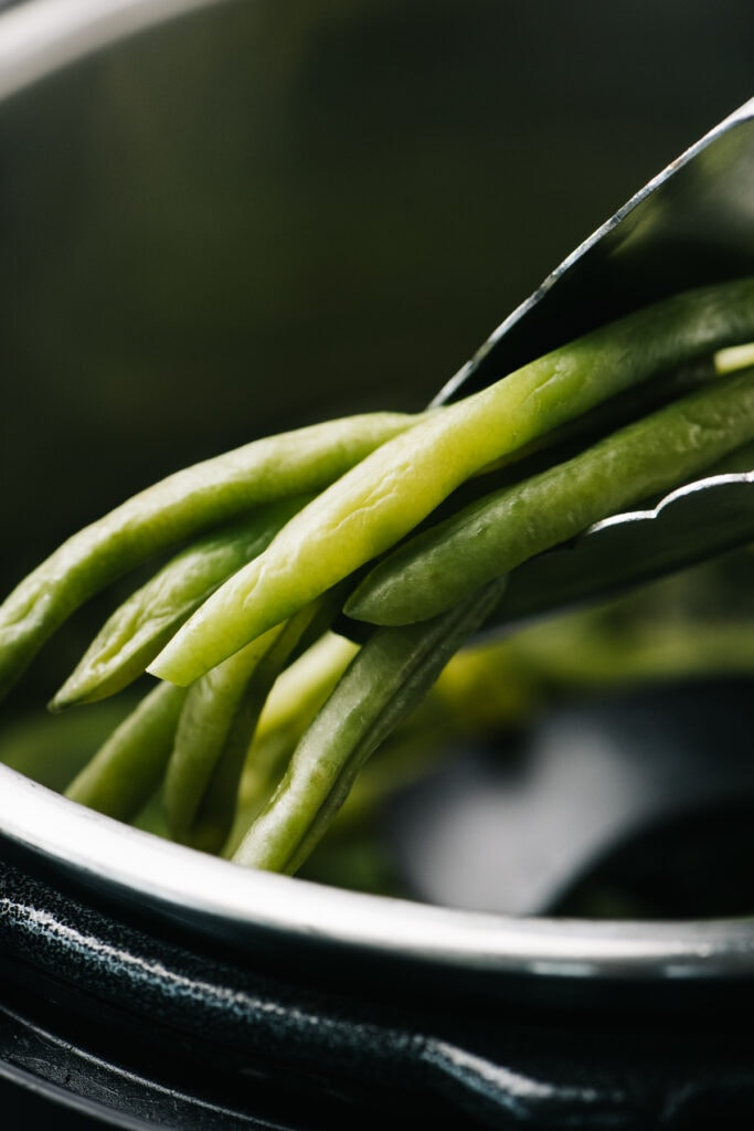 Tongs holding instant pot green beans.