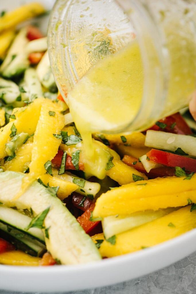 Pour lime vinaigrette over a mango salad.