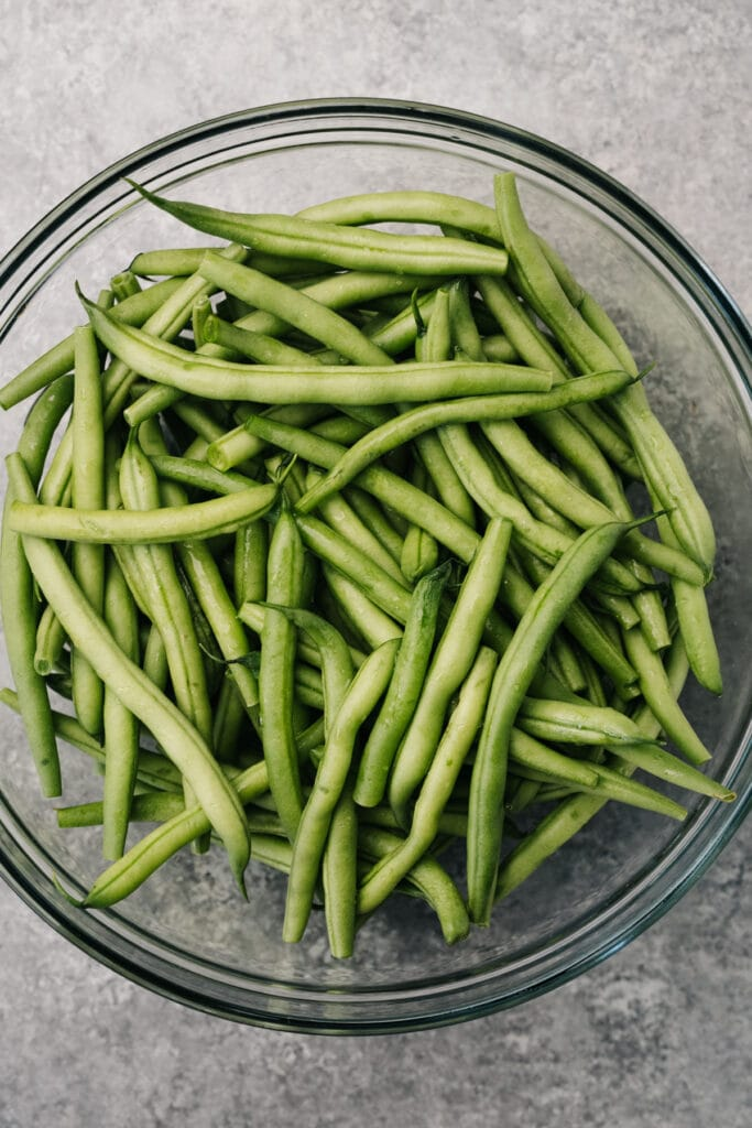 Raw green beans with water in glass microwave safe bowl.