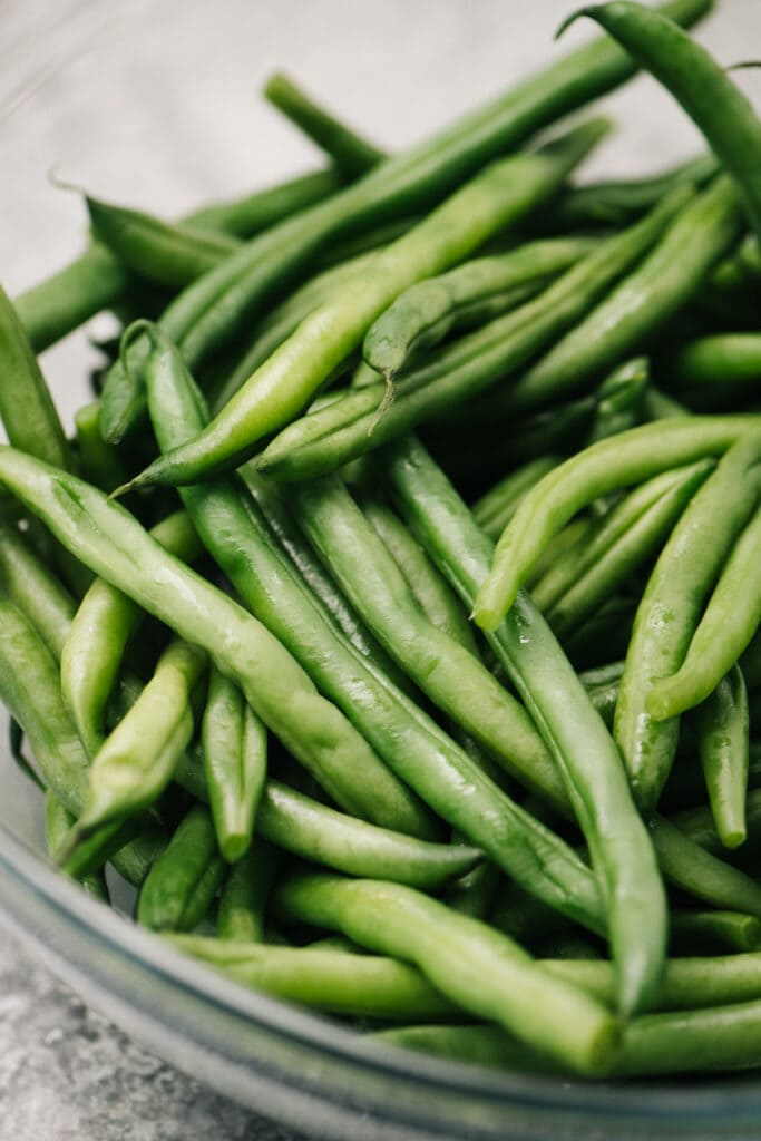 Side view, steamed green beans and water in a microwave safe bowl.
