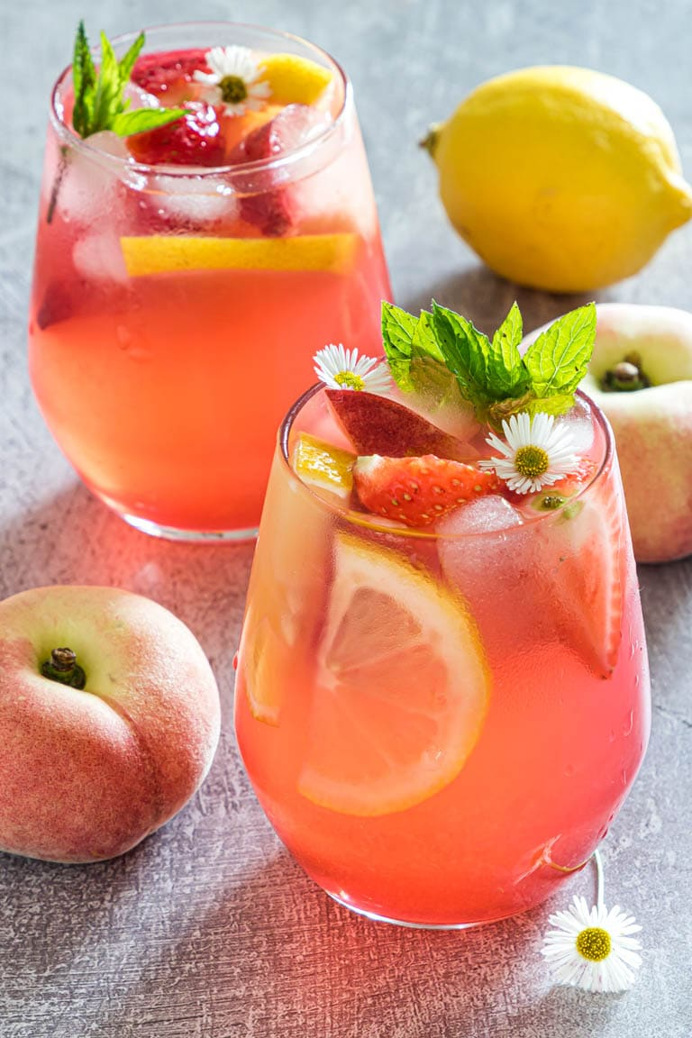 Two glasses of peach lemonade with peaches and lemons in the background.
