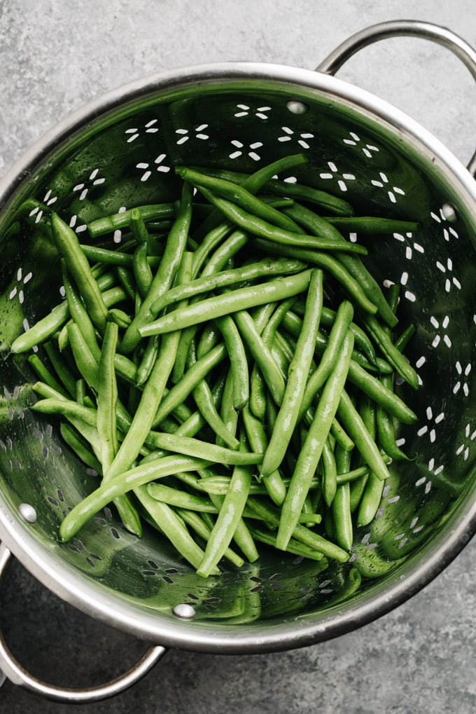 Trimmed and rinsed green beans in a metal colander.