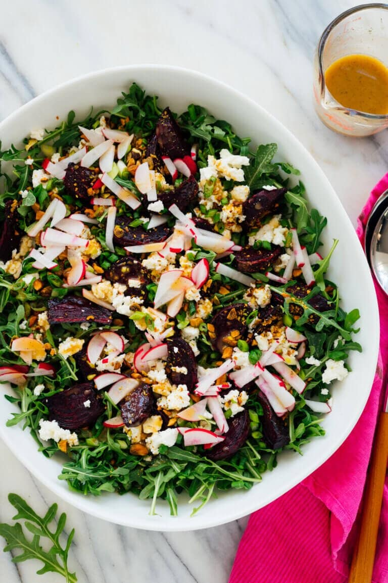 A vegetarian roasted beet dinner salad in a large white serving bowl on a marble table with dressing on the side.