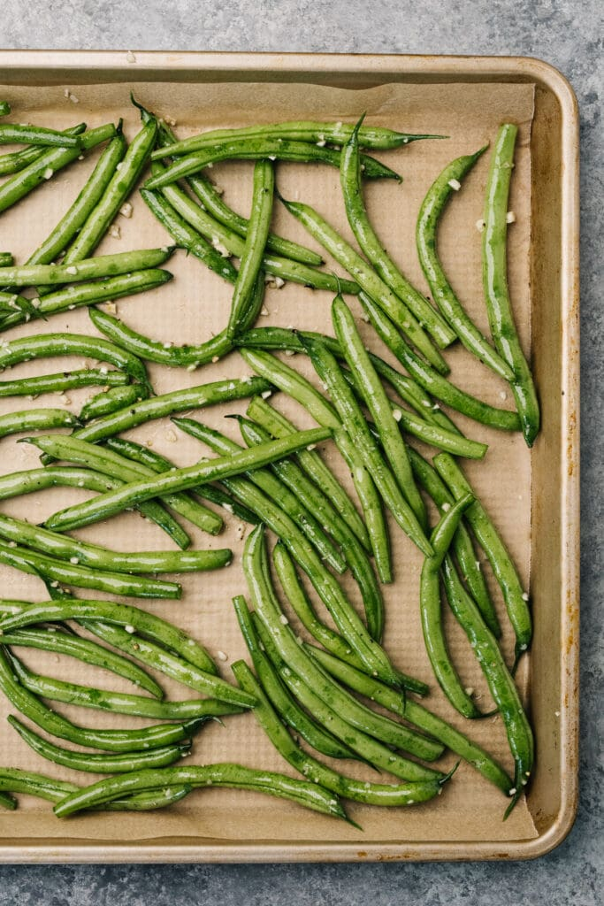 Green beans tossed with olive oil, garlic, salt and pepper on a parchment lined baking sheet.