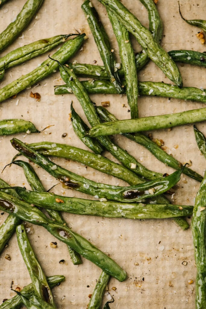 Roasted green beans on a parchment lined baking sheet.