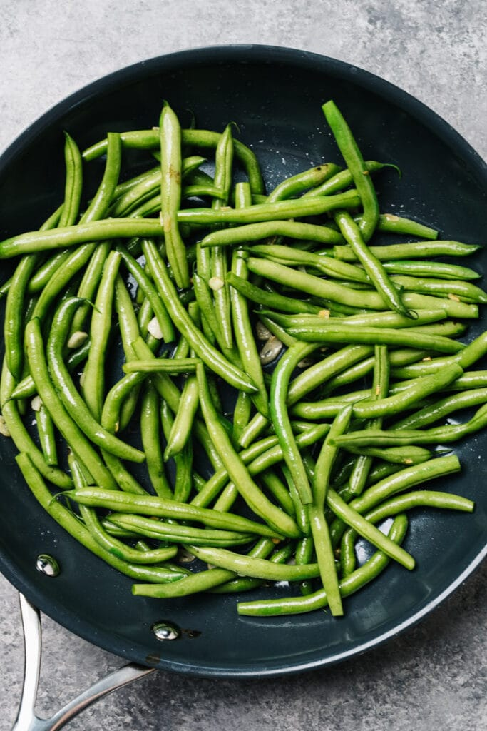 Green beans in a skillet with thinly sliced garlic.