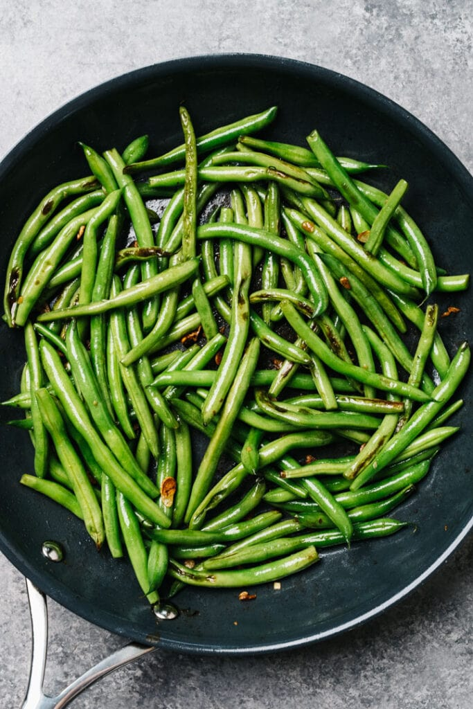 Sautéed green beans with garlic in a skillet.