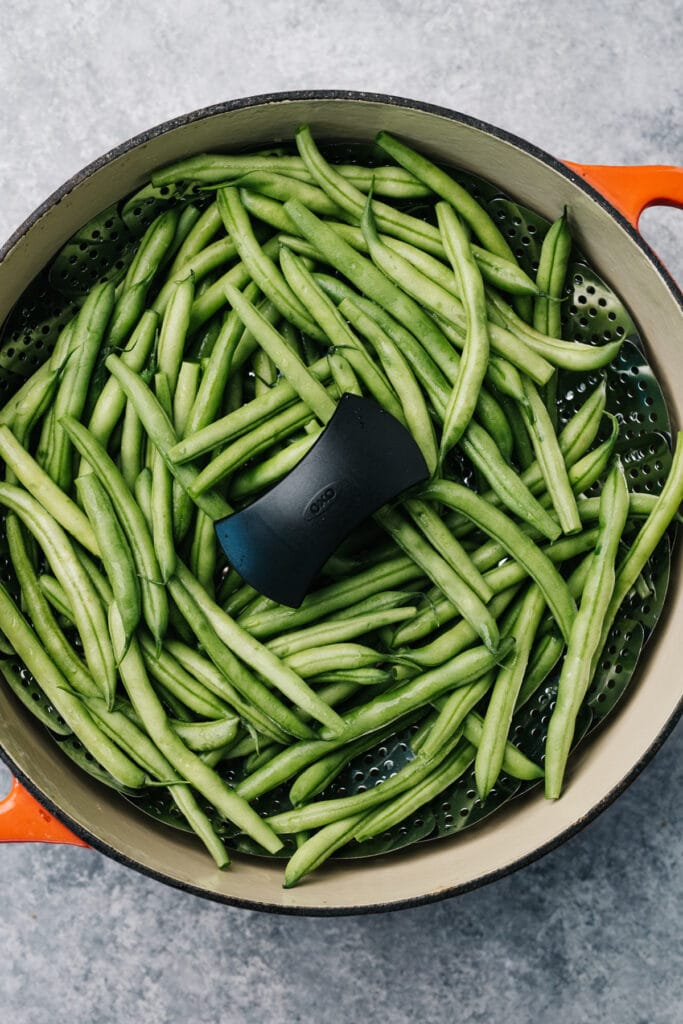 Green beans in a steamer basket fitted into a dutch oven.