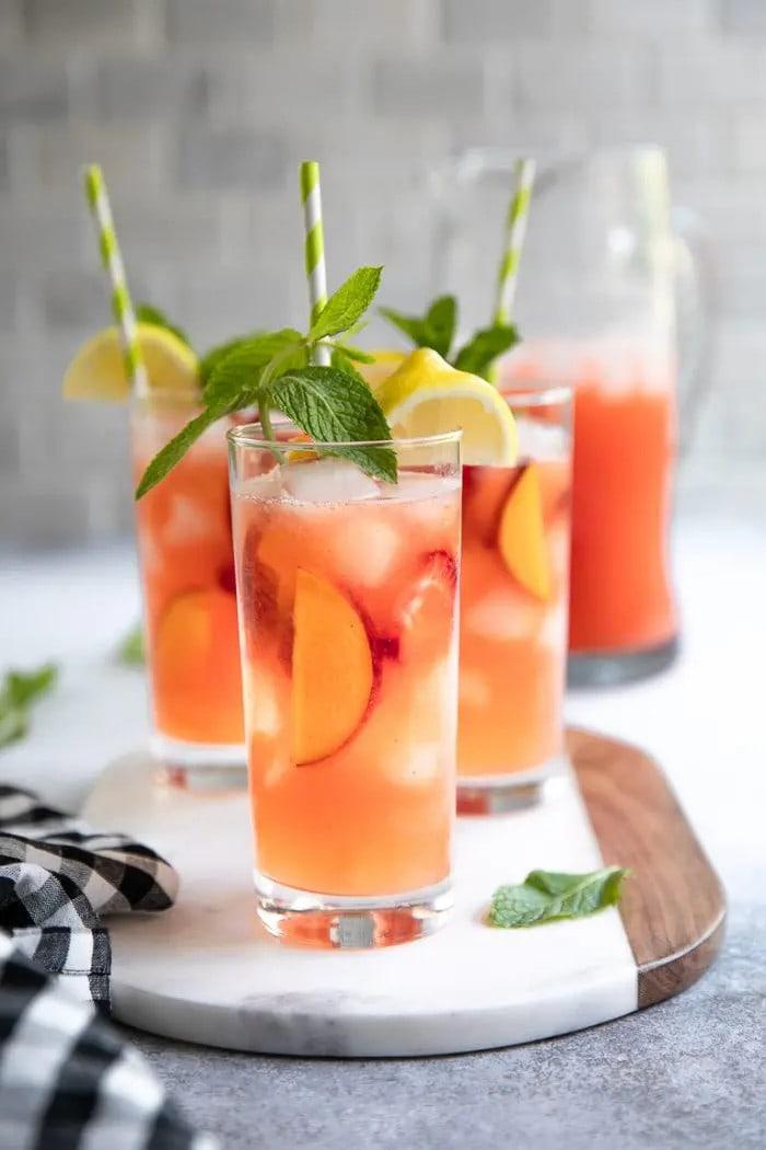 Three glasses of strawberry peach lemonade on a marble board.
