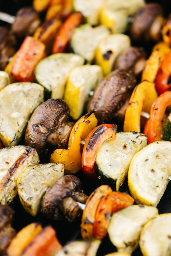 Side view, grilled veggie kabobs on grill grates.