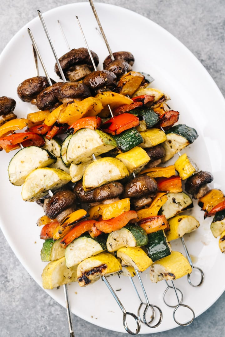 Vegetables kabobs with homemade marinade on a white platter.