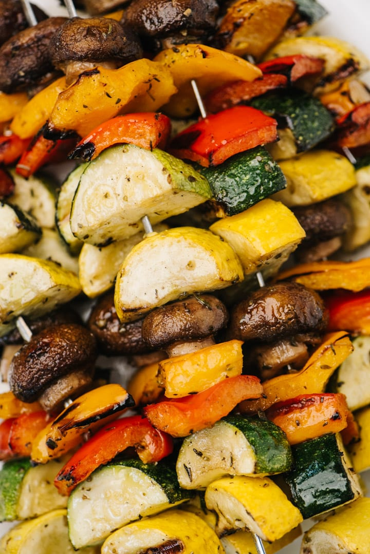 Vegetable kabobs stacked on a white serving platter.