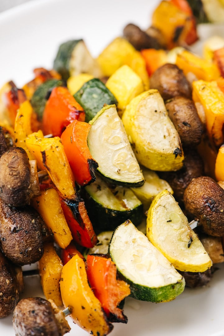 Side view, a stack of grilled veggie kabobs on a white platter.