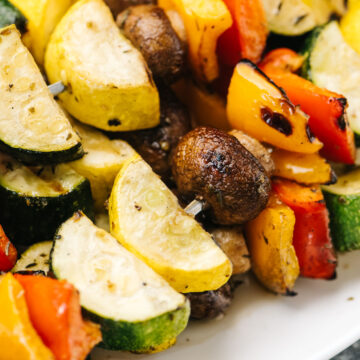 Side view, a stack of grilled vegetable kabobs on a white platter.