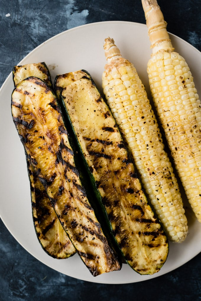 Grilled corn and grilled zucchini resting on a tan plate.