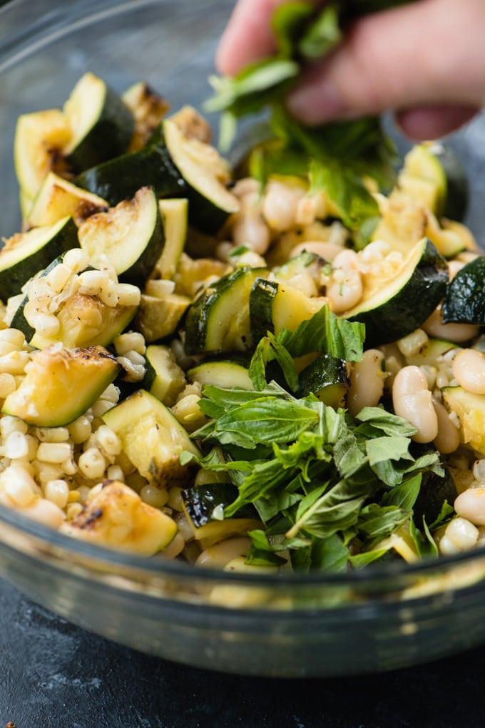 Adding fresh basil to a bowl of zucchini salad.