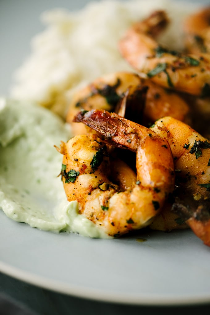 Side view, spicy sautéed shrimp with a dollop of avocado aioli.