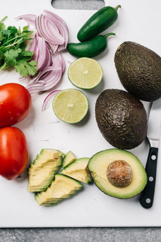 A halved avocado on a cutting board with whole avocados, plus limes, jalapeños, red onion, cilantro and roma tomatoes.