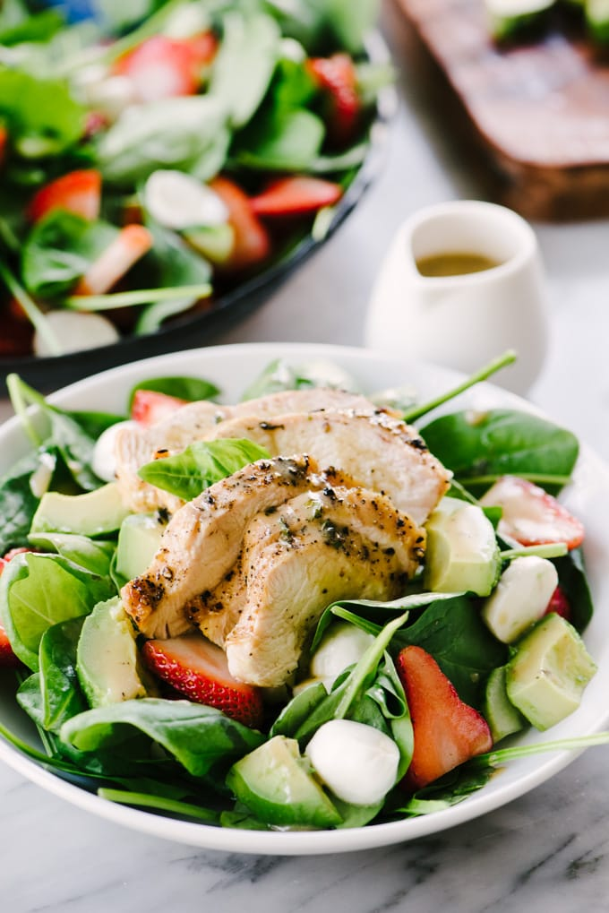 A strawberry avocado chicken salad in a white bowl with a large salad platter and small pitcher of dressing in the background.