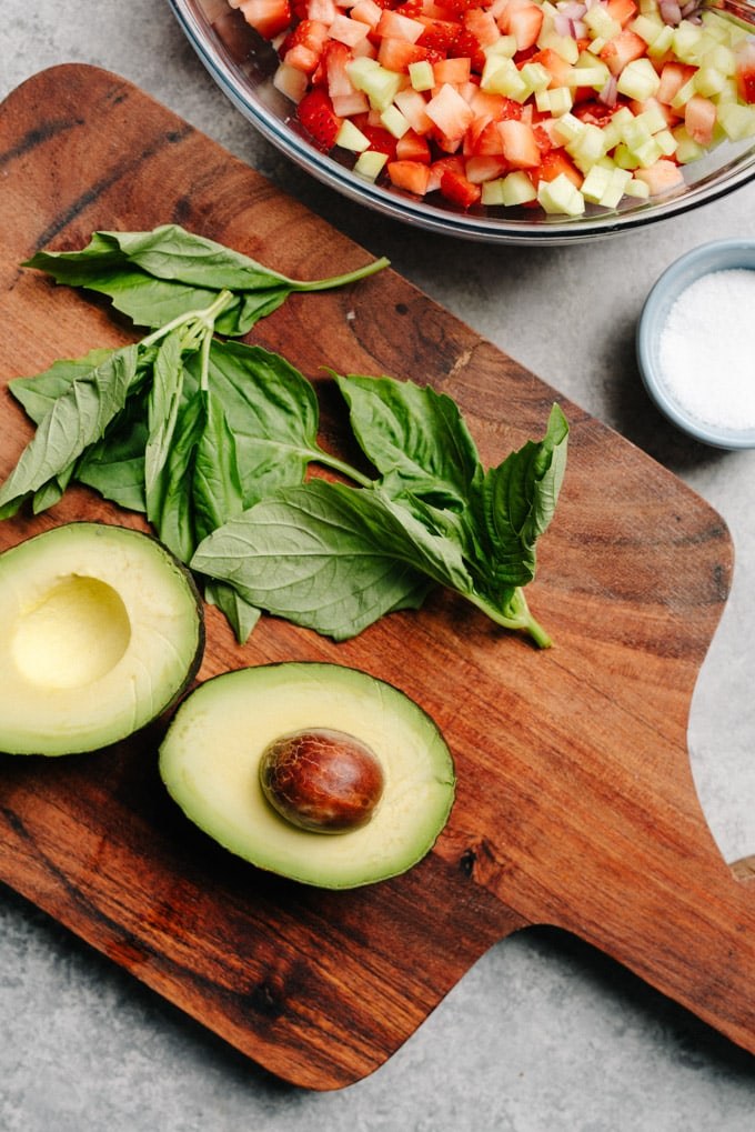 A halved avocado on a cutting board with basil leaves and salsa in the background.