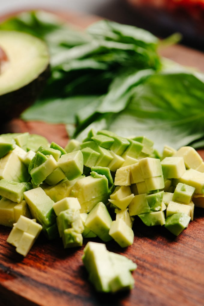 A diced avocado on a cutting board with basil leaves in the background.