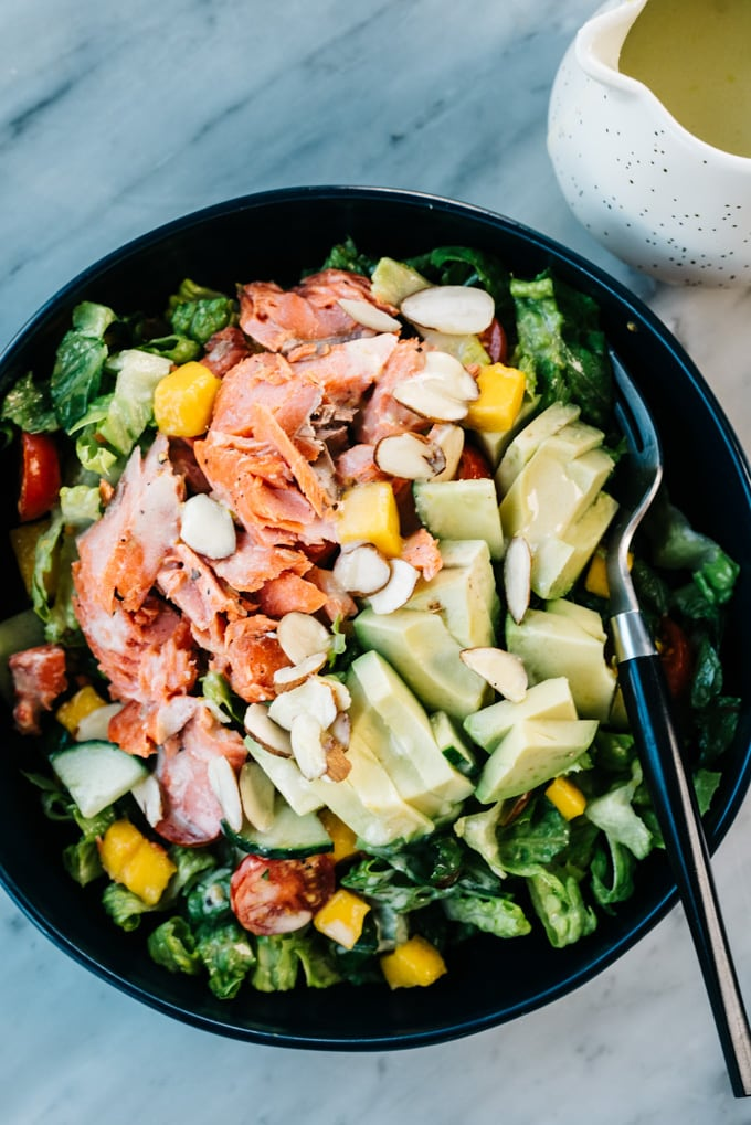 Salmon avocado salad in blue bowl with a silver fork and small pitcher of creamy lemon dressing.