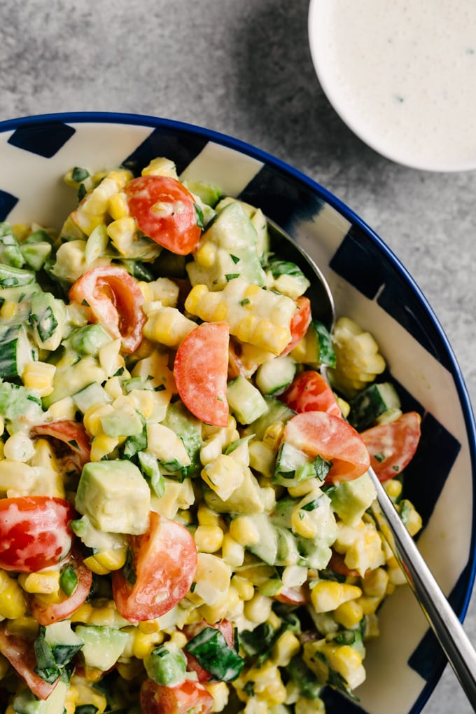 Avocado tomato corn salad in a blue and white patterned bowl with a small bowl of buttermilk dressing to the side.