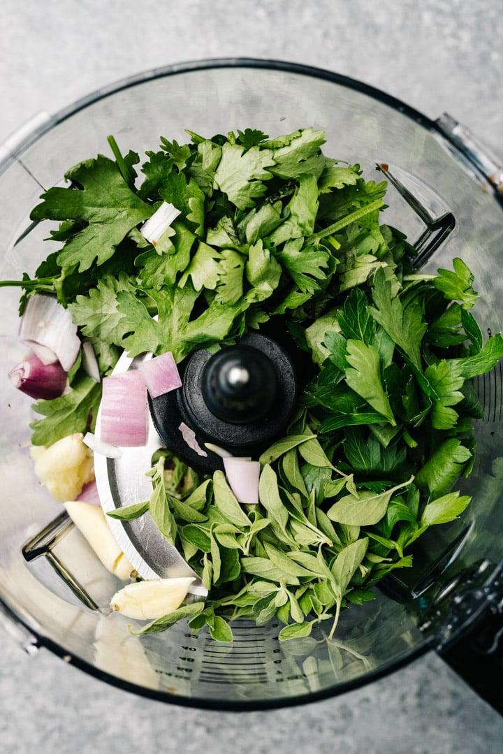 Cilantro, parsley, oregano, garlic, and shallot in the bowl of a food processor.