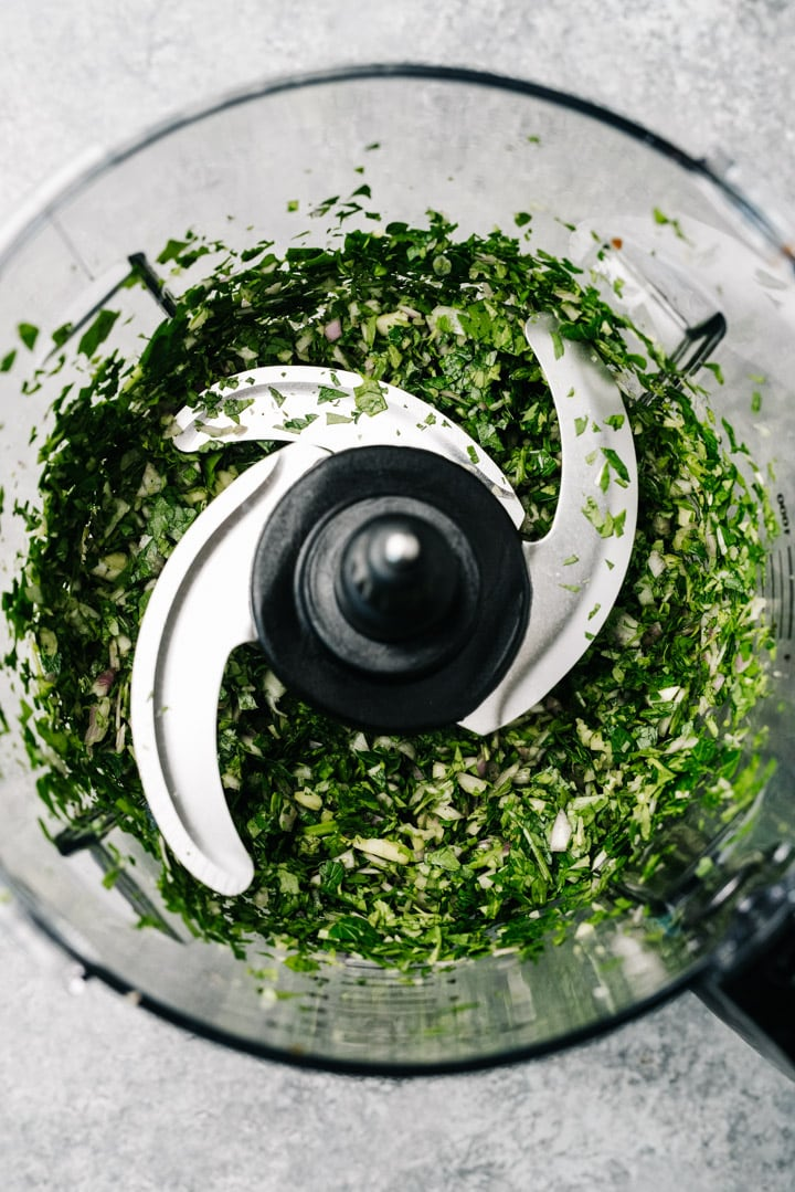 Minced herbs and garlic in a food processor.