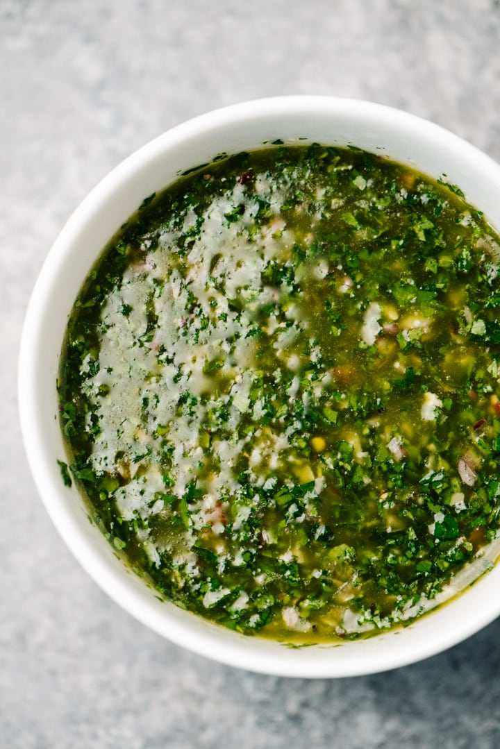 Chimichurri sauce in a white bowl on a concrete background.