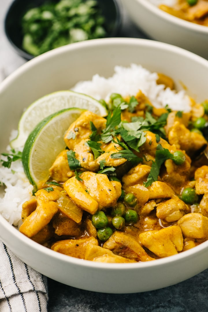 Side view, coconut chicken curry over white rice with cilantro in a bowl.