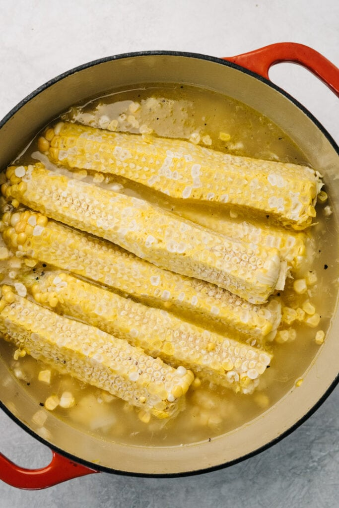 Stripped ears of corn sitting on top of corn soup before simmering.