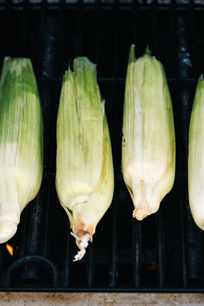 Four ears of corn in husks on a grill.