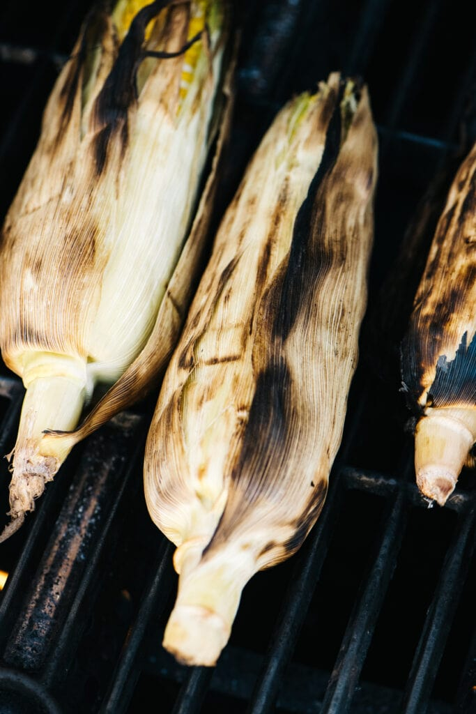 Four ears of corn on a gas grill, showing the husks very charred.