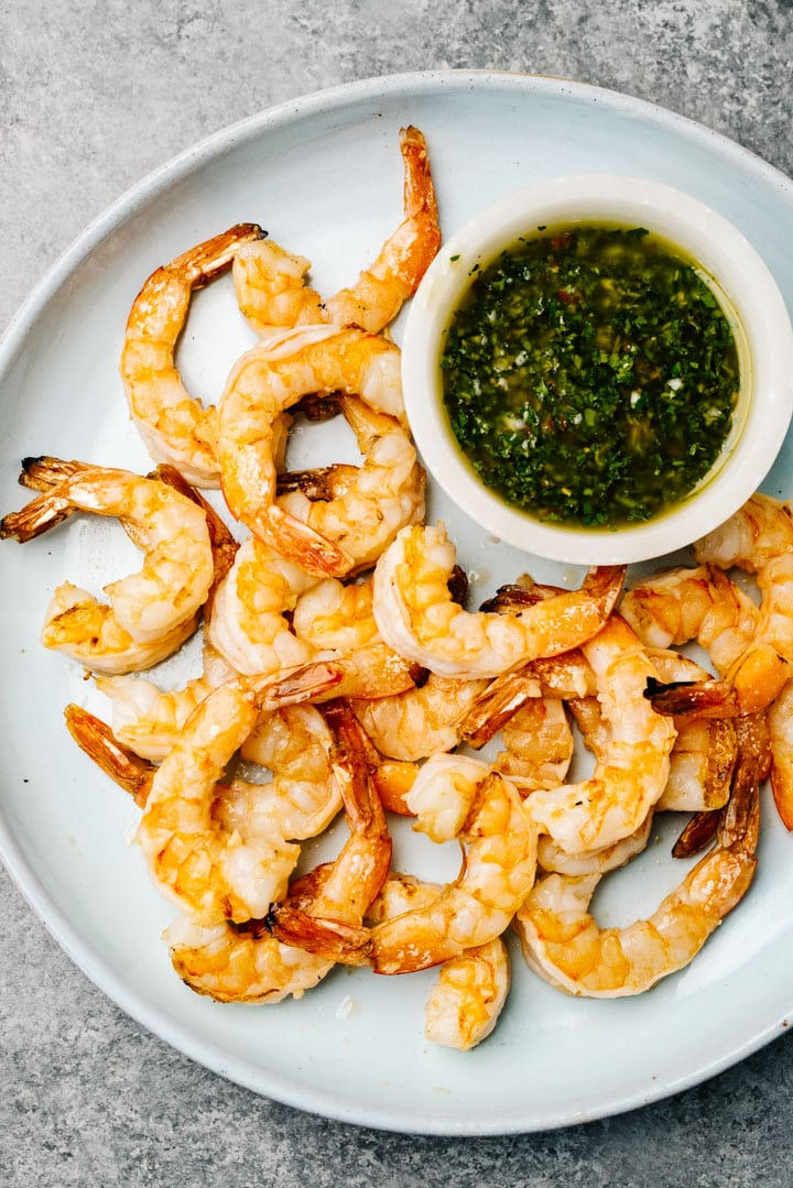 Grilled shrimp on a blue serving platter with a small dip bowl filled with chimichurri sauce.