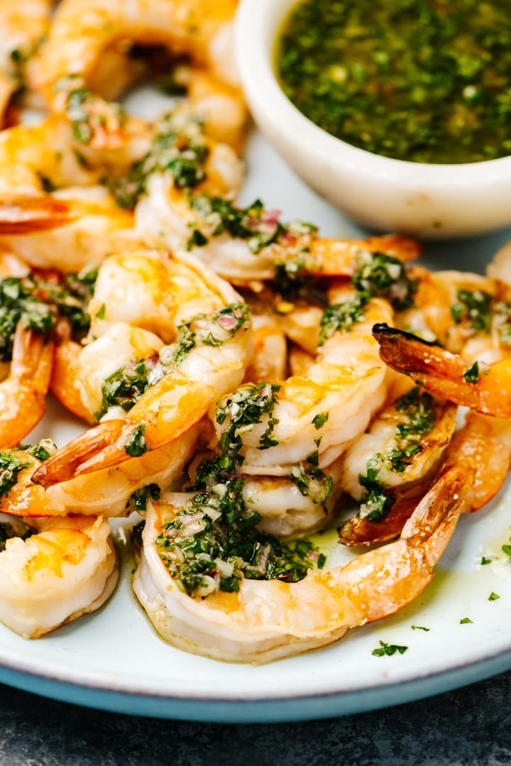 Side view, grilled shrimp drizzled with chimichurri sauce on a blue serving platter.
