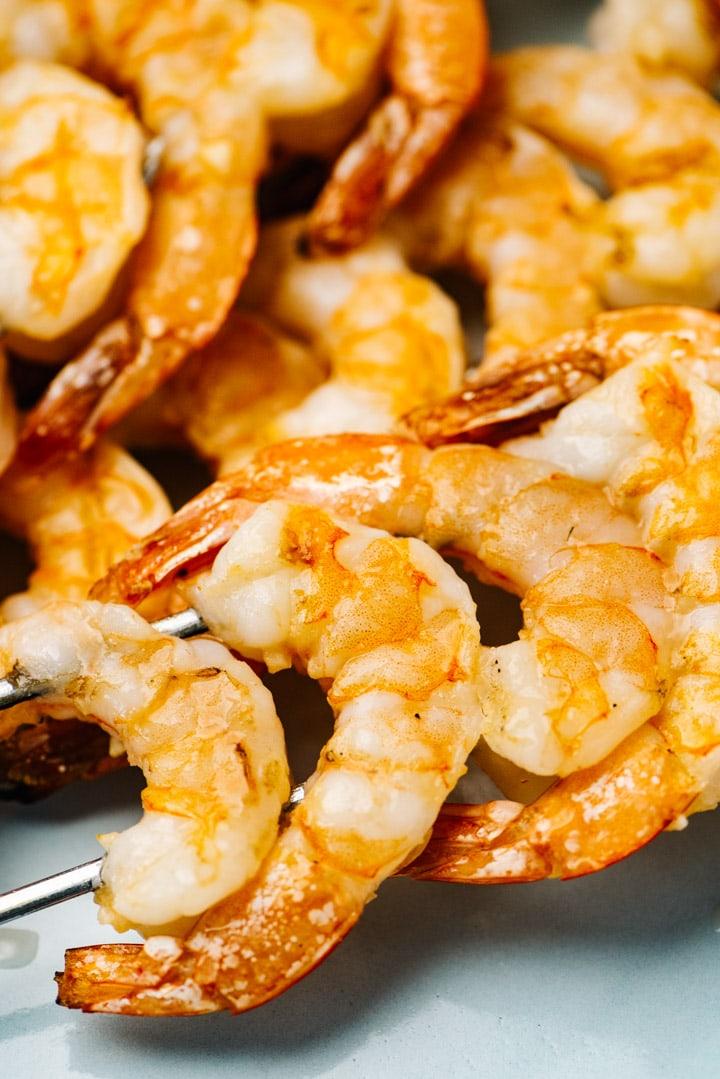 Side view, grilled shrimp skewers on a blue platter.