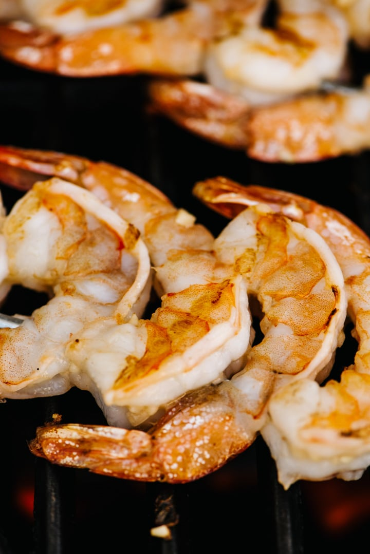 Side view, grilled shrimp on skewers on a gas grill grate.