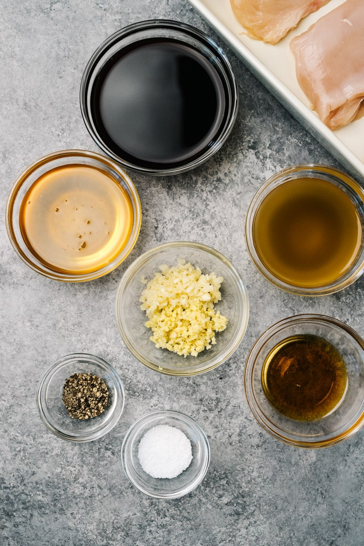 The ingredients for teriyaki chicken marinade in small glass bowls on a cement background.